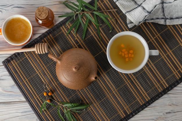 健康天然海クロウメモドキ茶とティーポットのテーブルの上に蜂蜜