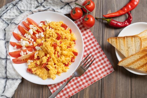 Яичница-болтунья с перцем, помидорами и сыром на завтрак.
