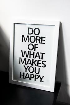 Мотивационные слова делай больше того, что делает тебя счастливым на фоторамке у белой стены