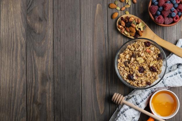 ガラスのボウルにナッツ、蜂蜜、果実の健康的な自家製グラノーラ。オーバーヘッドフラットレイ