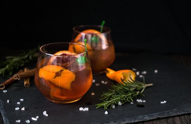 Коктейль негрони на черном подается с ломтиком апельсина и розмарина.
