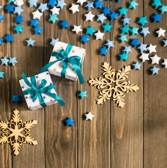 Рождественская композиция с подарками, декоративными снежинками и бумажными звездами