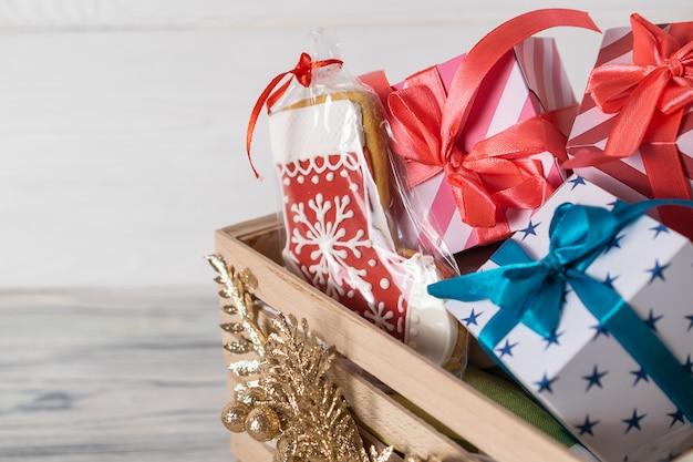 Подарки на рождество и глазированное печенье в украшенной деревянной коробке. крупный план