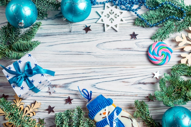 モミの木の枝、青いボール、プレゼント、雪だるまクッキーで飾られたコピースペースの背景を持つクリスマスフレーム