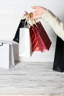 手にショッピングパッケージを保持している幸せな女。紙袋。店頭での販売。顧客がプレゼントを購入します。ブラックフライデーのセール。休日の特別オファー、割引。市場の女性