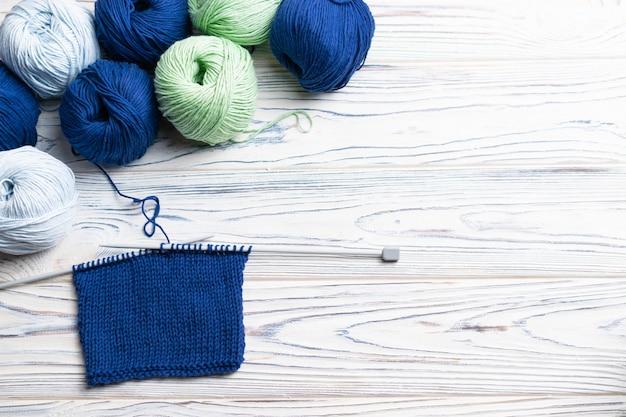 編み物が進行中。青と緑の糸と白い木製の背景に針でフラットレイアウト構成。