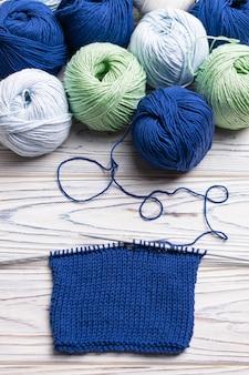 編み物が進行中。青と緑の糸と針でフラットレイ構成