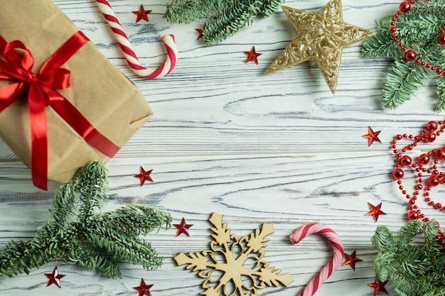 モミの木の枝、プレゼント、キャンディケイン、雪片、星とクリスマスフレームの背景の装飾