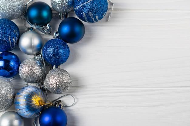 青と銀の輝くクリスマスボールでお祭りの背景。テキストのコピースペースを持つフラットレイアウト