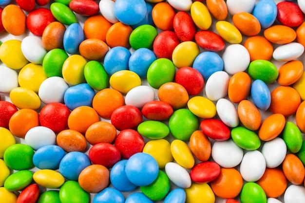 チョコレート艶をかけられたキャンディーと明るいカラフルな背景