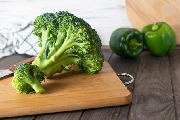 キッチンで木の板に新鮮な有機緑ブロッコリー成分