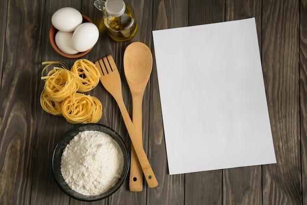 Рецепт макета на деревянной поверхности чаши с мукой, макаронами, яйцами, маслом в бутылке, деревянной ложкой и вилкой