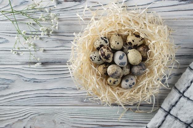Пестрые перепелиные пасхальные яйца в сенном гнезде