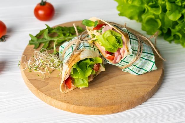 Шаурма завернутый бутерброд с салатом из помидоров ветчиной и сыром на деревянной тарелке