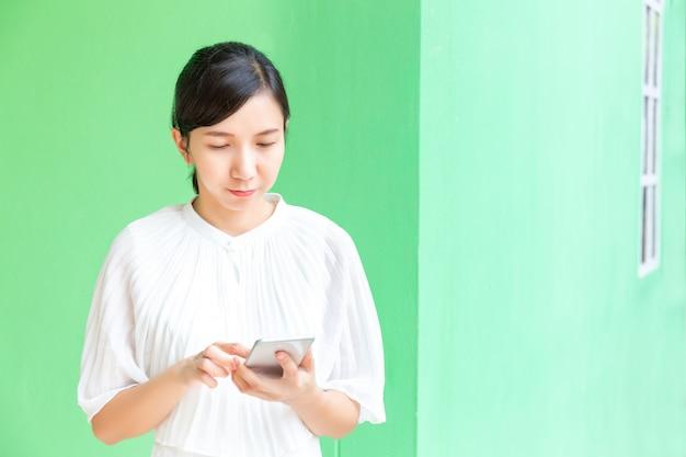 緑のパステル調の背景に携帯電話オンラインショッピングで働くビジネス女性。