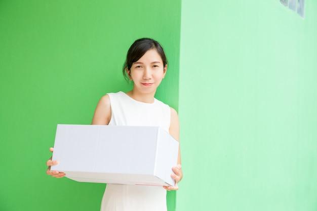緑のパステル調の背景に小包ボックスオンラインショッピングで働くビジネス女性。