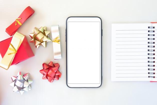 スマートフォンとギフトカード、空白の画面との紙の接触