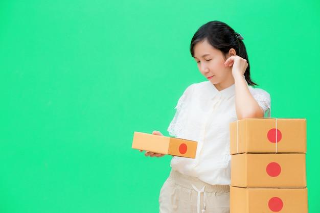 若い女の子は配達のための小包箱を準備します。