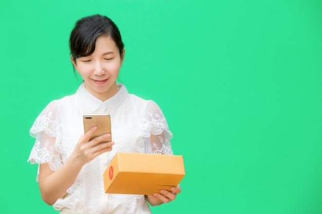 幸せな女の子は小包を受け取ったオンラインショッピングを配信します。