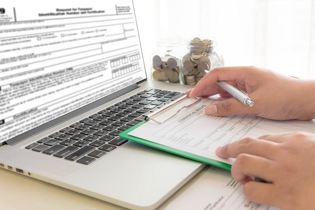 Бизнесмен высчитывает счеты в рабочем месте с компьтер-книжкой на офисе.