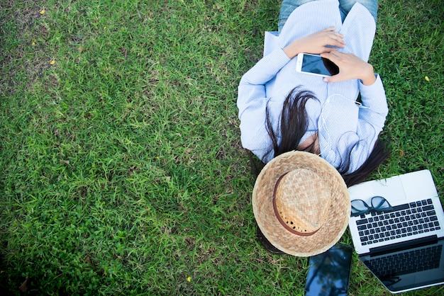 ラップトップのスマートタブレットとスマートフォンを使用してフリーランスは、緑の芝生のフィールドを読むスプレッドシートに横たわっていました。