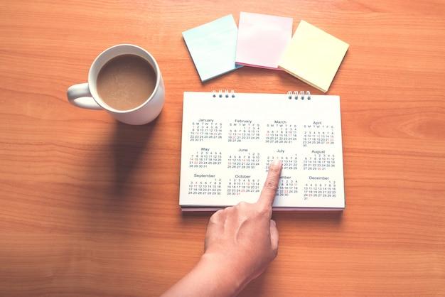 カレンダーで旅行計画を立て、木製のテーブルでコーヒーを飲みながらメモにポストイットを使用する