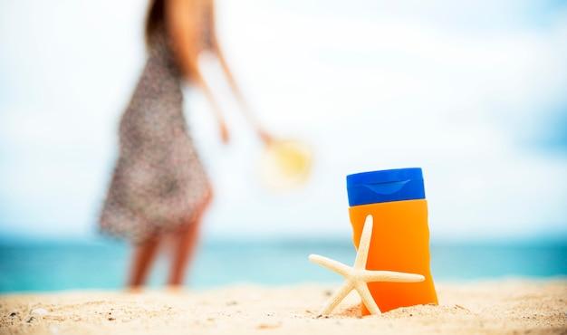 Солнцезащитный лосьон защищает женскую кожу на тропическом летнем открытом пляже.