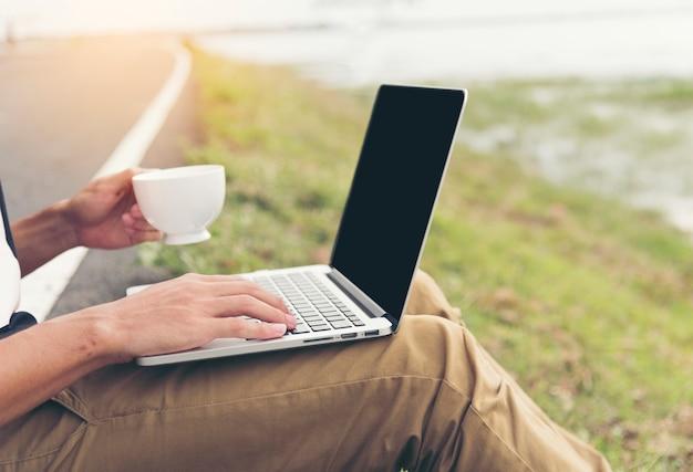 Закройте вверх руки красивого человека, используя ноутбук, держа чашку кофе в кафе на открытом воздухе. фриланс работает на открытом воздухе. стиль жизни нового поколения работает внештатным сотрудником.