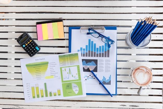 Взгляд сверху молодой работницы используя компьтер-книжку и читающ отчет, диаграммы, диаграммы, документ на работе. бизнес женщина, работающая на ее столе.