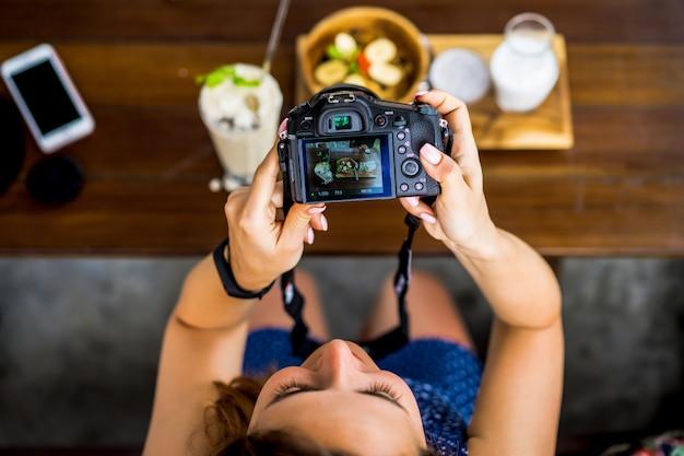美しい女性はカメラに彼女の食べ物を写真します。