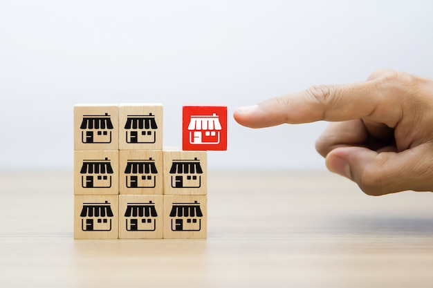 Рука бизнесмена выбирает деревянный блог с магазином значков маркетинга франшизы.