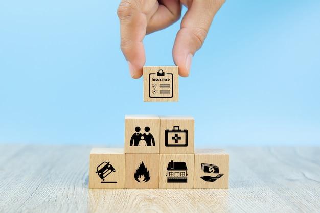 クローズアップ手は安全家族保険の保険アイコンが付いた赤い木のおもちゃブロックを選択してください