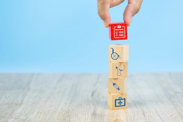 クローズアップの手は、健康保険の概念のための保険証券のアイコンが付いた赤い木のおもちゃのブロックを選択します。