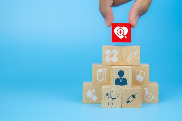 クローズアップ手は、医療と健康保険の概念のためのピラミッドの形で積み重ねられたハートのアイコンが付いた立方体の木製おもちゃのブロックを選択します。