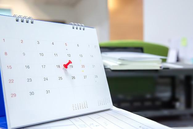 Штырь красного цвета на концепции календаря для плановика событий.