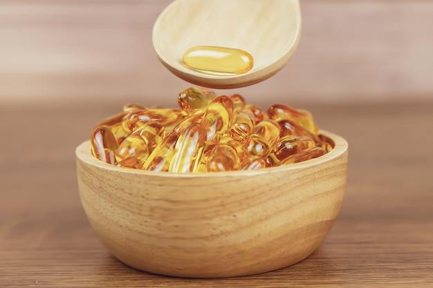 Куча капсулы масла печени трески в деревянной ложке.