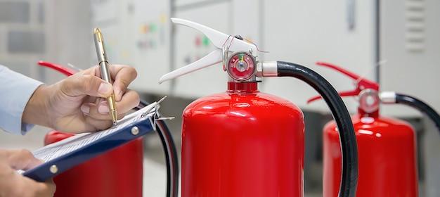 エンジニアは消火器タンクをチェックおよび検査しています。