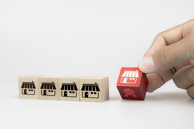 Рука выбирает куб деревянные игрушки блоги с франшизой маркетинговой магазин значок и значок диаграммы.
