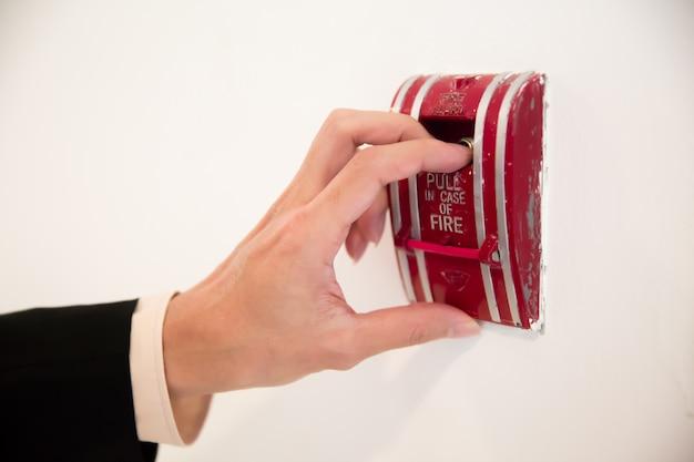 火災の場合にスイッチを引くためのクローズアップ手。