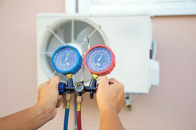 Руки техника используют измерительный инструмент для проверки вакуумный насос откачивает воздух для кондиционера.
