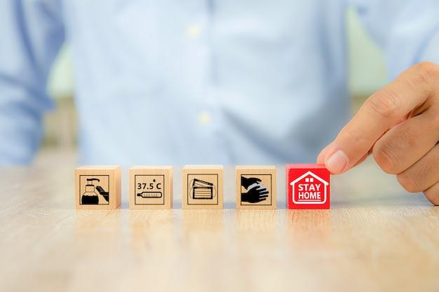 Рука выбрать значок остаться дома на деревянном блоке