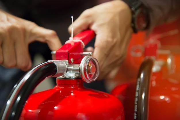 エンジニアは消火器の安全ピンを引っ張っています。