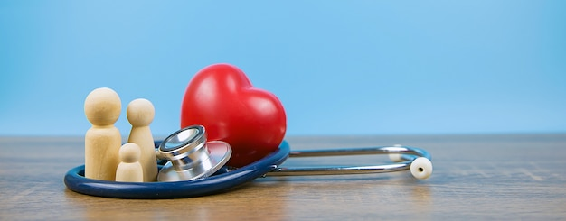 Семья с стетоскопом и красным сердцем, концепцией медицинского осмотра и медицинской страховкой.