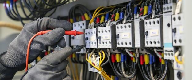 回路ブレーカーで電流電圧をチェックするデジタルマルチメーターを使用する電気技師。