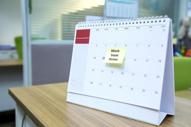 Календарь на столе с бумажной запиской работы из дома.