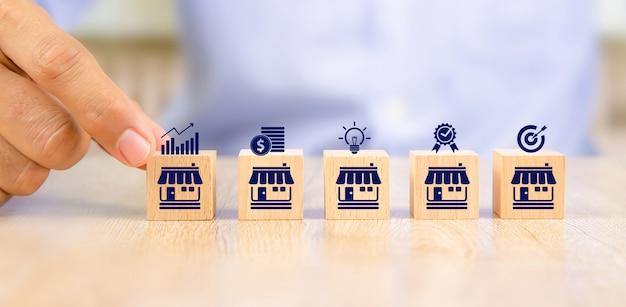 クローズアップ手は、フランチャイズビジネスストアのアイコンに合わせてキューブ木製おもちゃブロックの場所を選択します。