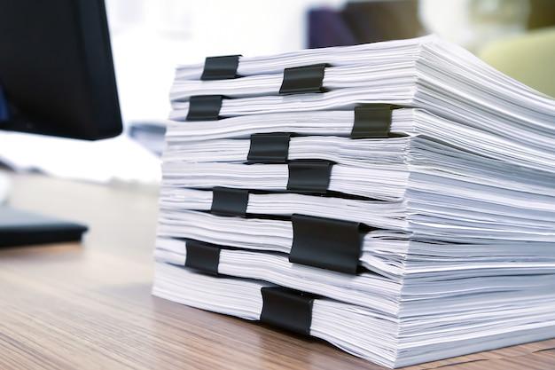 机の上に積み上げたたくさんの紙と書類の山