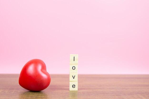Красные воздушные шарики в форме сердца с деревянным игрушечным блоком