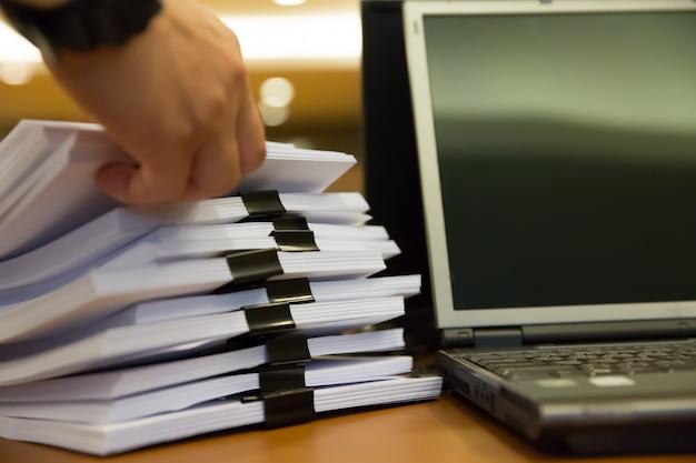 作業デスクオフィスの情報を検索するためのスタック紙で働くビジネスマン。