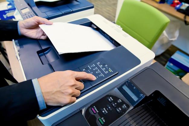 クローズアップショットビジネスマンはコピー機を使用しています。